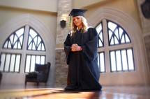 girl in her cap and gown on her knees in prayer