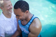 Man baptizing a man in a pool of water.