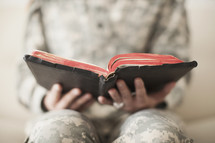 Female soldier holding an open Bible.