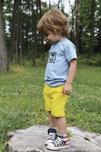a toddler boy standing outdoors looking down at the ground