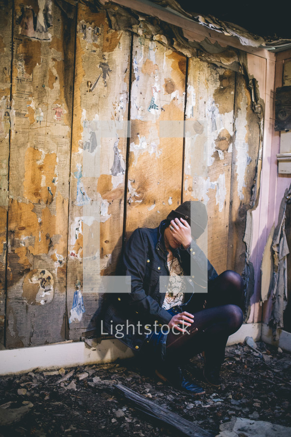 A woman sits in an abandoned house with her face in her hand.