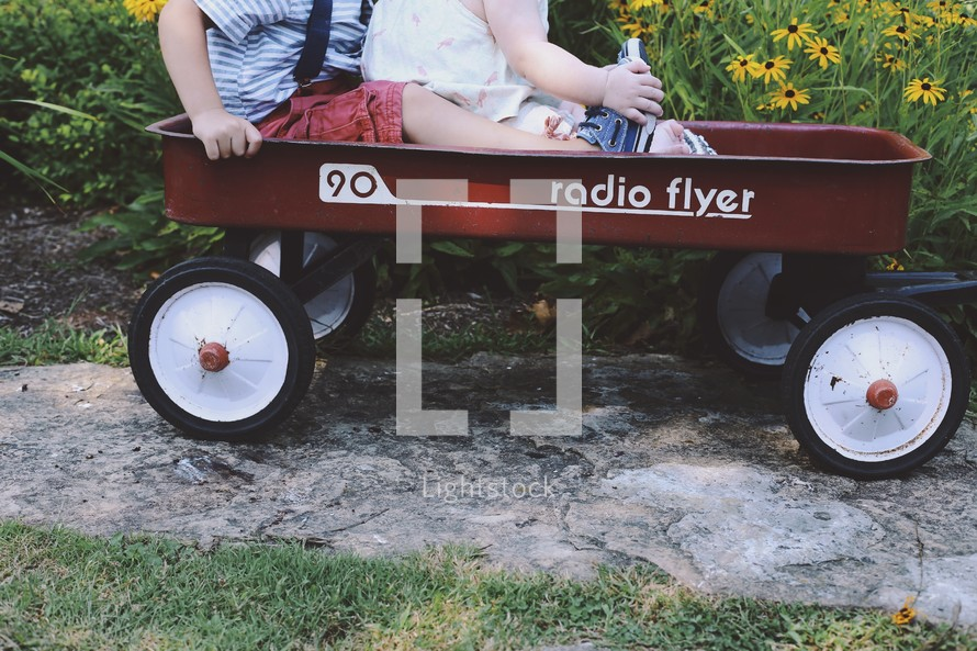 a brother and sister riding in a red wagon