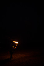 a man walking with a burning flame through darkness