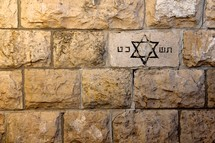 Jewish star of David carved into a brick in a limestone wall in Jerusalem.