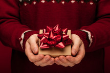 a man holding a Christmas gift in cupped hands