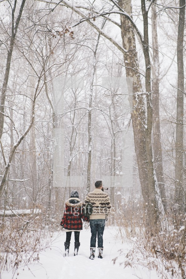 a couple standing outdoors in the snow