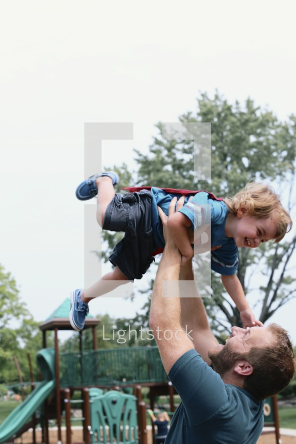 a father holding his son in the air at a playground