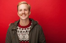 man with a mustache in a Christmas sweater and coat