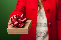a woman in a red peacoat holding a Christmas gift box