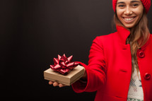 a woman in a red peacoat holding a gift box for Christmas