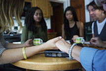 woman's group Bible study having holding hands in prayer  in a living room