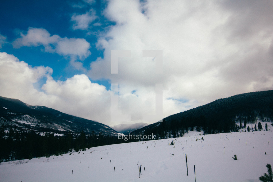 clouds over a snow covered landscape
