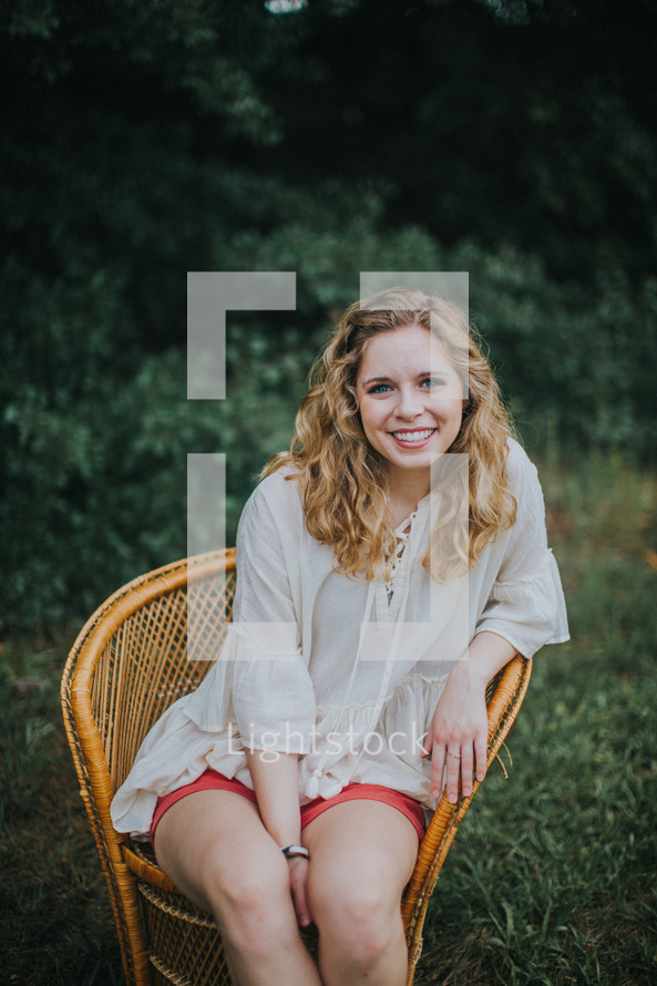 portrait of a smiling teen girl sitting in a wicker chair outdoors