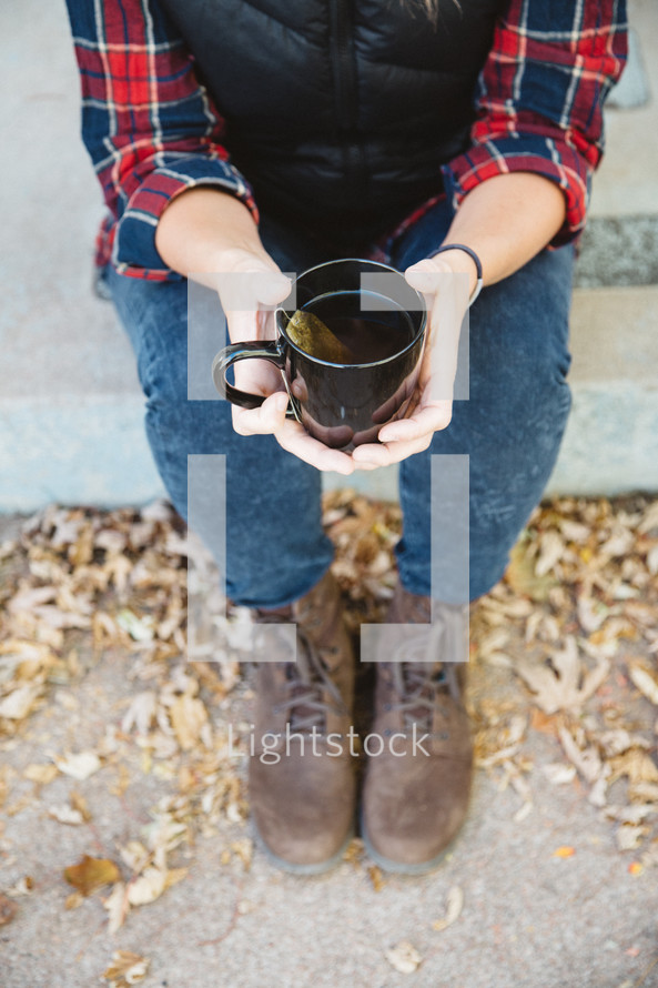 a woman sitting on a curb holding a mug of tea