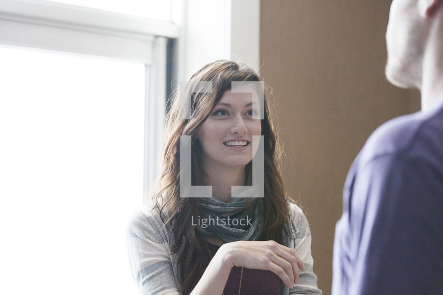 A man and woman in conversation in front of a window