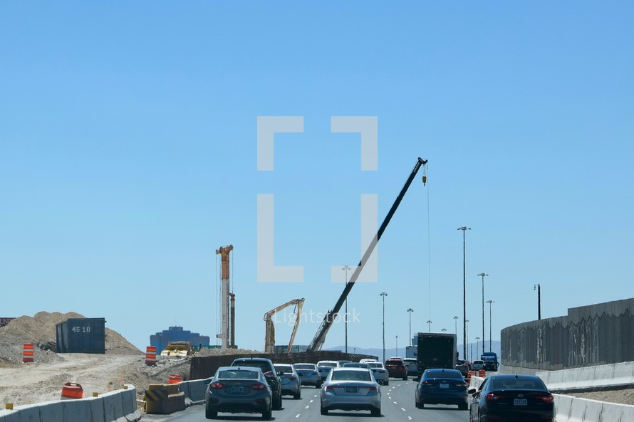 construction cranes over a freeway under construction