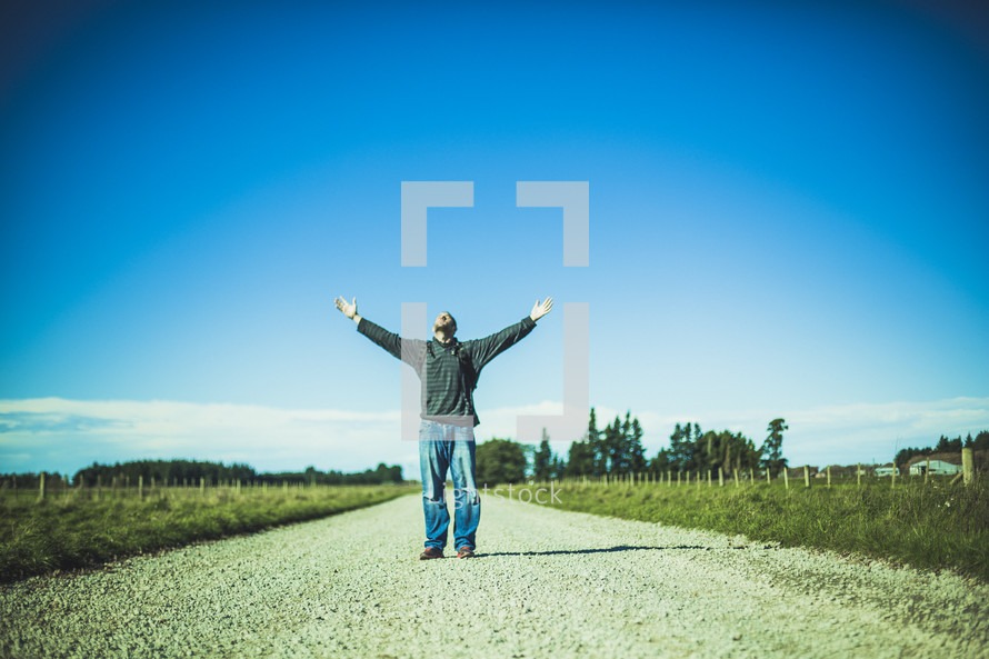 man standing in the middle of a road with hands raised to God
