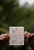 a man holding up a thank you card