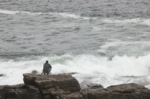 man watching waves crashing into rocks