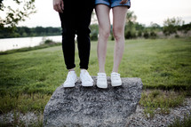 legs of a couple standing on a rock