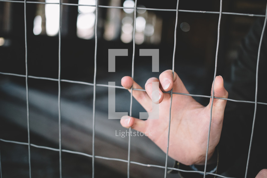 A woman's hand grasps a wire fence.