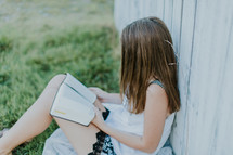teen girl reading a Bible leaning against a fence