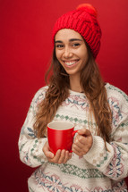 a woman in a winter sweater and hat holding a mug