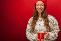 a woman in a sweater and beanie holding a mug