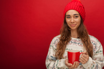 a woman in a sweater holding a mug