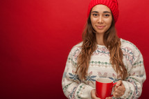a woman in a wool cap holding a mug