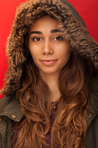 a headshot of a woman in a winter coat with a hood