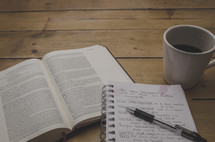 open Bible, coffee mug, pen, and notes on a notepad
