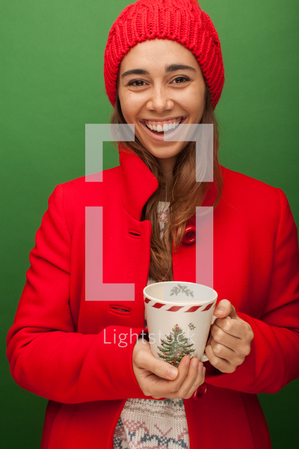 a woman in a red trench coat holding a mug