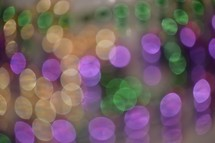 Festive Fat Tuesday bokeh lights in traditional Mardi Gras Purple, Gold, and, Green colors