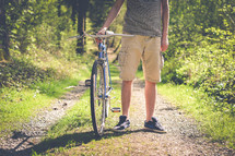a man standing on a gravel path next to a bicycle