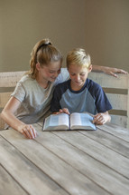 a brother and sister reading a Bible
