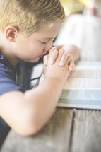 a boy reading a Bible and praying