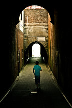 man walking down an alley and brick tunnel