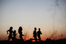 silhouettes of young adults running outdoors at sunset