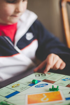 A young boy plays a board game.