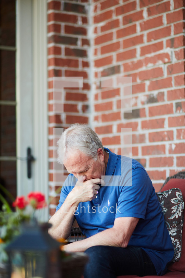 a man sitting on a porch with head down