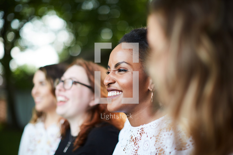 faces of a group of women standing in a row outdoors