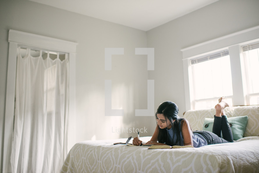 A teen girl studying while laying on a bed.
