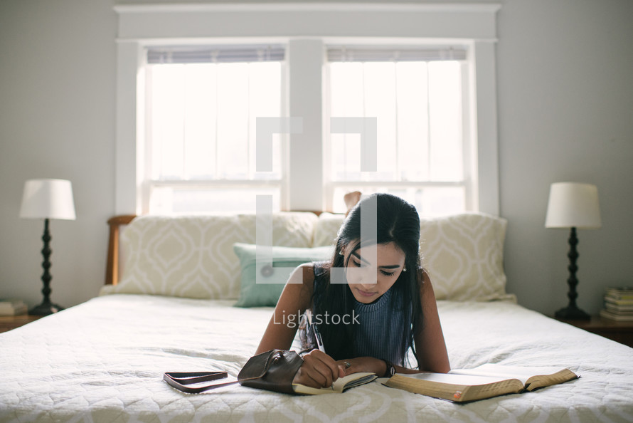 A teen girl taking notes and studying the Bible on her bed.