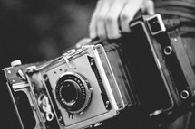 a man holding an antique box camera