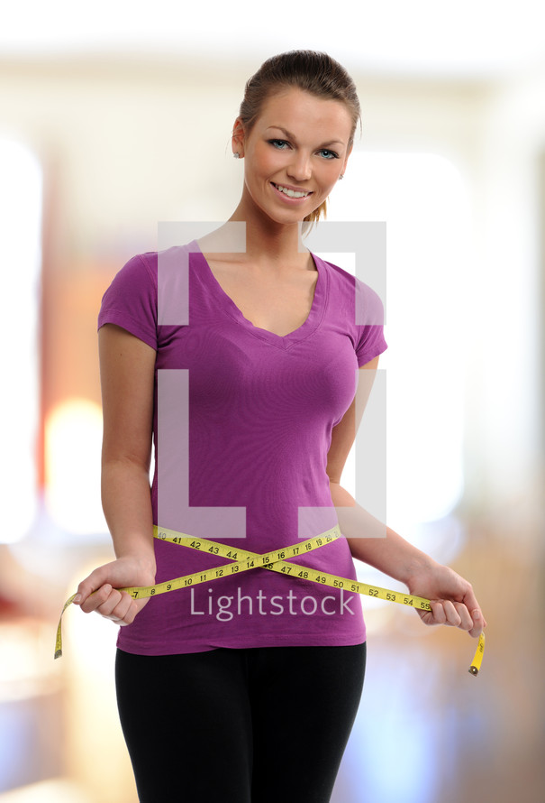 woman holding measuring tape around her waist
