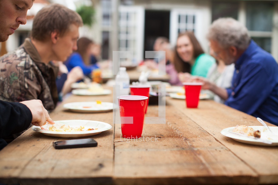 family at a picnic table eating outdoors