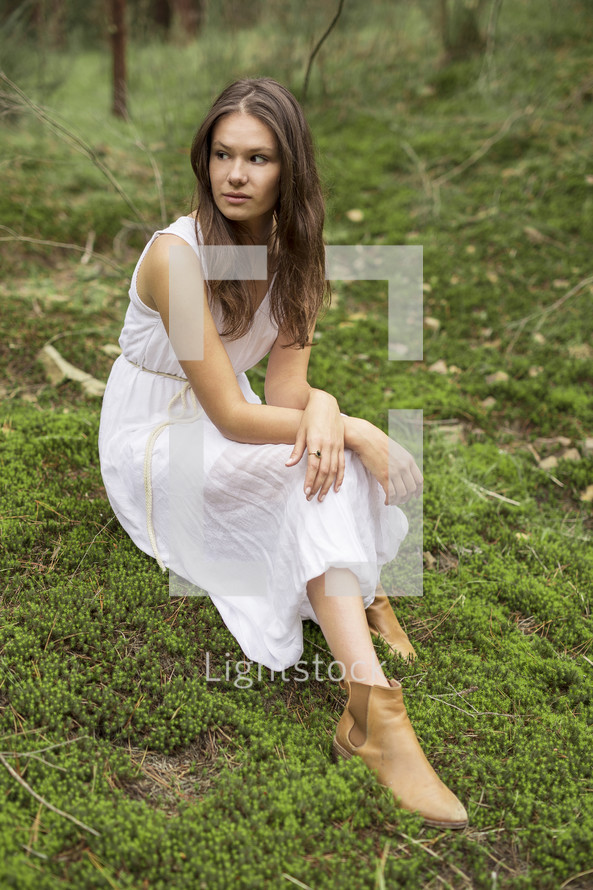 a young woman in a dress sitting on mossy ground