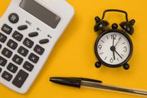 pen, calculator, and alarm clock