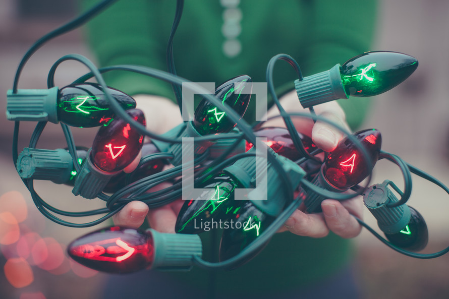 A woman holds a tangle of red and green Christmas lights in her hands.